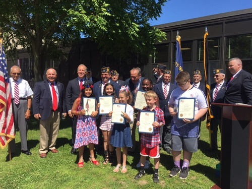 Councilman Cochrange, Students, and representatives from American Legion Post 411, gather on the lawn in front of the American Flag
