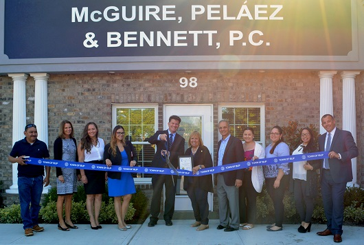 Supervisor Carpenter standing in front of the new McGuire Law firm entrance with full associates and staff holding ribbon for the ribbon cutting