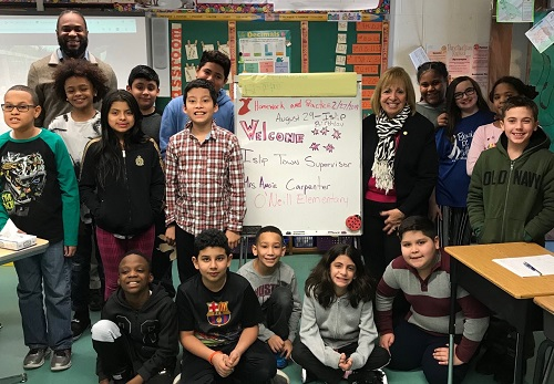 Supervisor Carpenter stands with the literacy students in a classroom near an easle with a handdrawn welcome sign the students wrote to welcome her