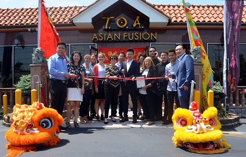 Supervisor Carpenter, ToA  Staff, Sayville Chamber of Commerce personel stand infront of the new ToA location on a bright sunny day, colorful dragon costumes at the bottom of the frame