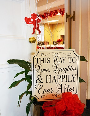 The Town Board Room Doors half open with a sign saying This Way to Love, Laughter and Happily Ever After, with the decorated Town Board room seen in the background
